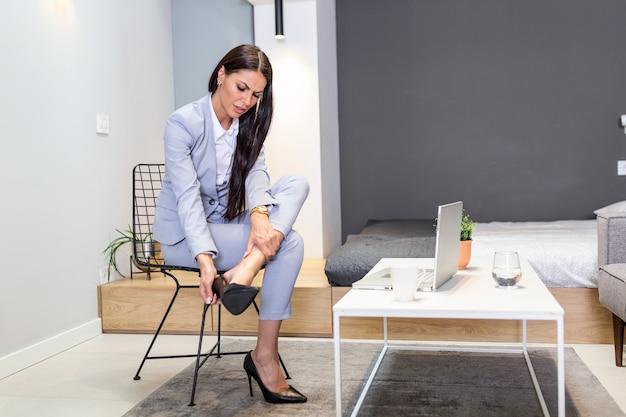 Femme d'affaires décollant des chaussures à talons hauts après le travail à la maison.
