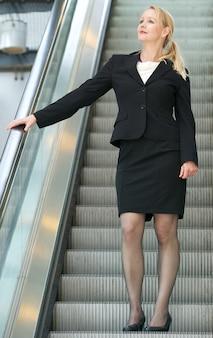 Femme d'affaires en descendant l'escalator