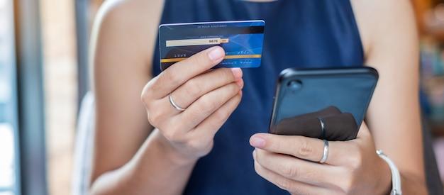 Femme d'affaires détenant la carte de crédit et à l'aide de smartphone