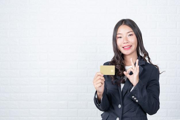 Femme d'affaires détenant une carte de paiement séparée, mur de briques blanches fait des gestes avec la langue des signes.