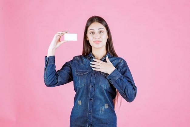 Femme d'affaires détenant une carte de visite et pointant sur elle-même
