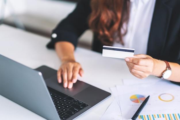 Une femme d'affaires détenant des cartes de crédit tout en utilisant un ordinateur portable au bureau