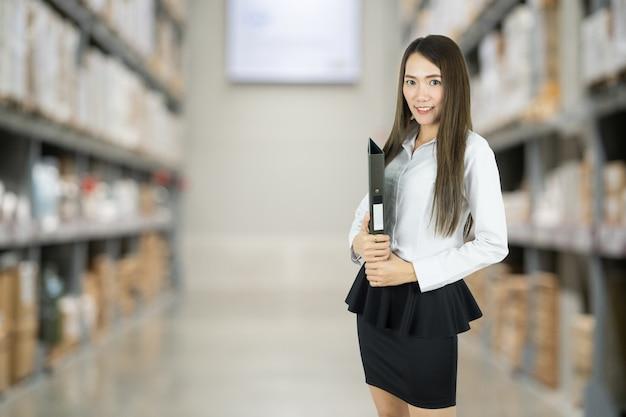 Femme d'affaires détenant le document sur le fond de l'entrepôt.