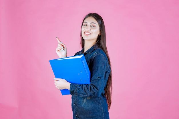Femme d'affaires détenant un dossier de rapport bleu et pointant vers le haut