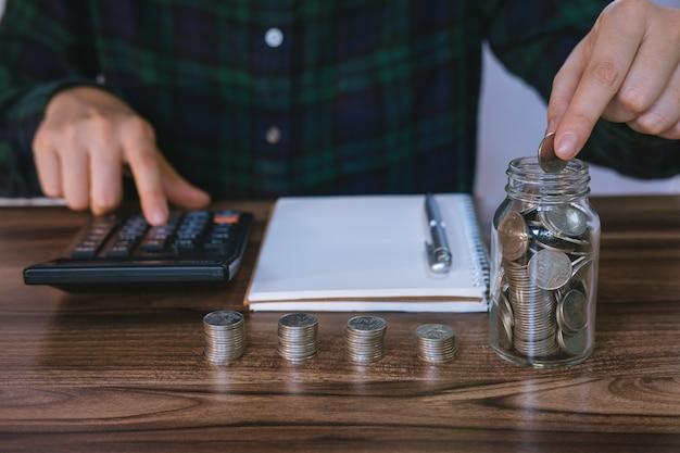Femme d'affaires détenant des pièces de monnaie mise en verre et analyse des comptes financiers sur le bureau.