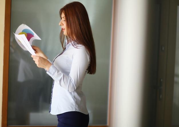 Femme d'affaires détenant des rapports et regardant la caméra. espace de copie