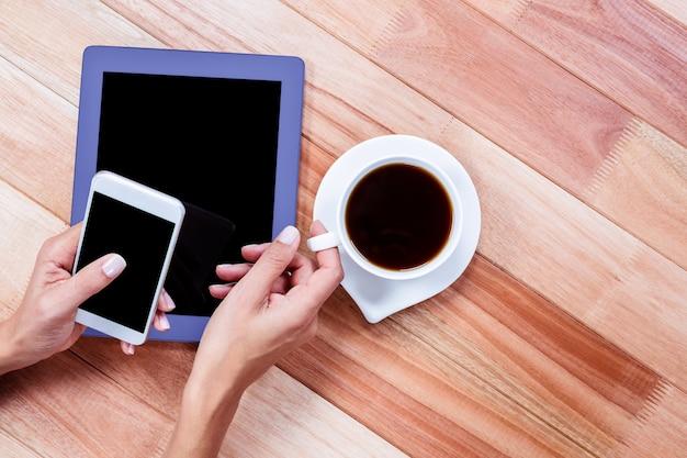 Femme d'affaires détenant un smartphone et une tasse de café