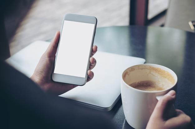 Femme d'affaires détenant un téléphone mobile avec écran blanc vide avec latop