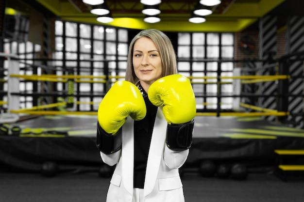 Une femme d'affaires déterminée et élégante en gants de boxe jaunes jette un coup de poing à la caméra sur fond de ring de boxe.