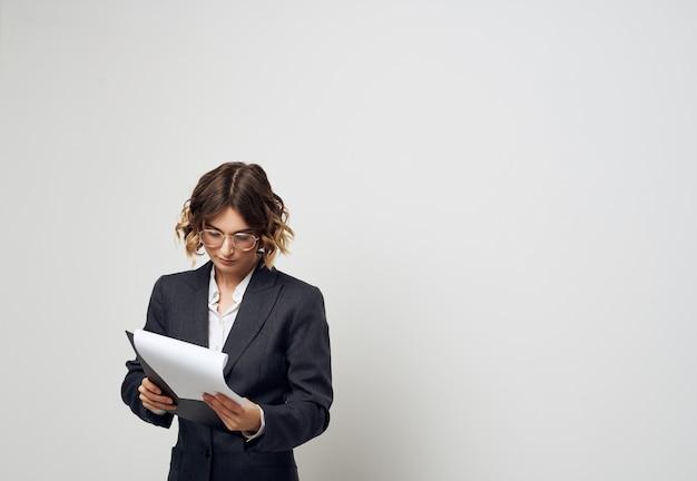 Femme d'affaires avec des documents en mains sur une lumière à l'intérieur