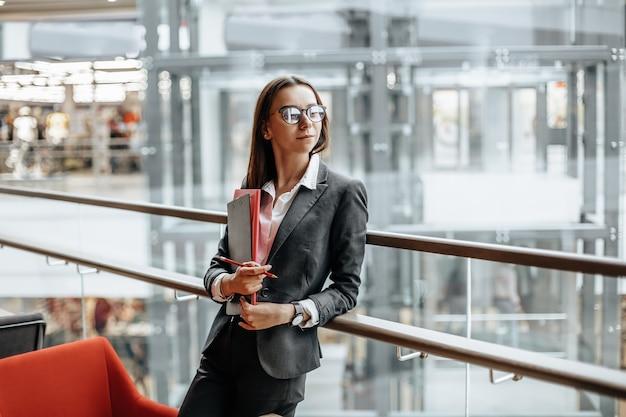 Femme d'affaires avec des documents pour le travail. fille étudiante avec des dossiers avec de la documentation. un agent recueillera les informations.