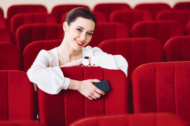 Femme d'affaires avec des documents et téléphone assis sur une chaise de sièges