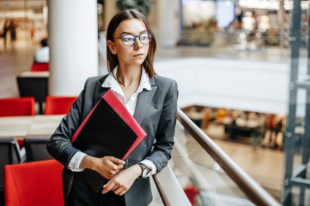 Femme d'affaires avec des documents de travail. fille étudiante avec des dossiers avec documentation. un agent recueillera des informations.