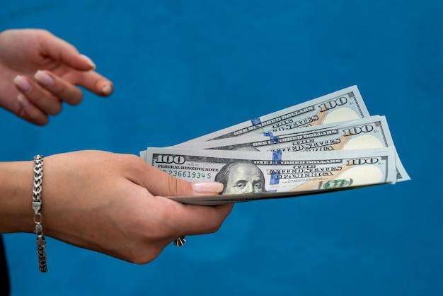 Femme d'affaires avec des dollars isolés sur bleu. concept de finance
