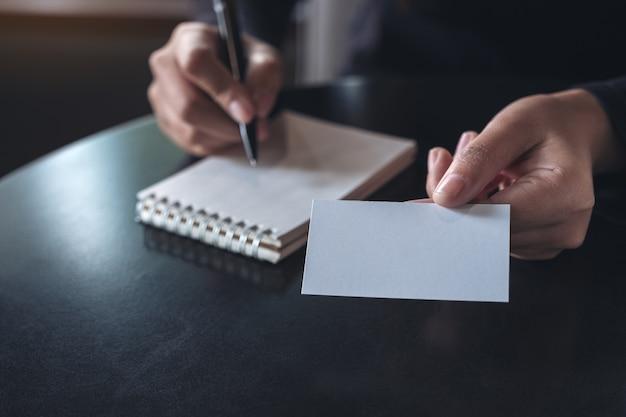 Femme d'affaires donnant et montrant une carte de visite vide tout en écrivant sur un cahier