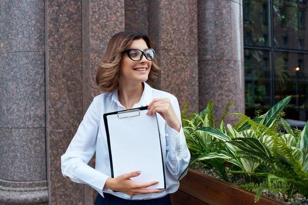 Femme d'affaires avec dossier pour papiers fond clair professionnel