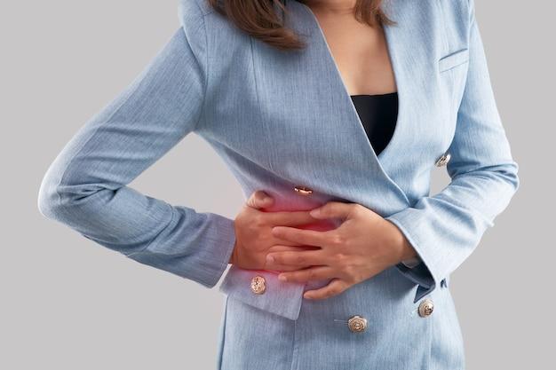 Femme d'affaires avec douleur dans le dos. sur fond gris