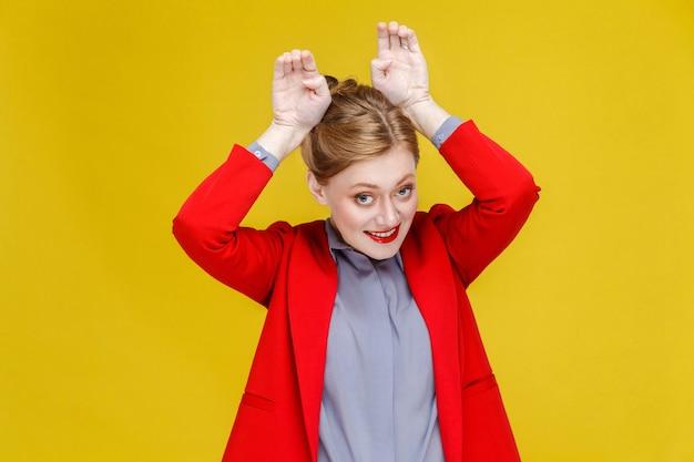 Femme d'affaires drôle en costume rouge montrant le signe du lapin