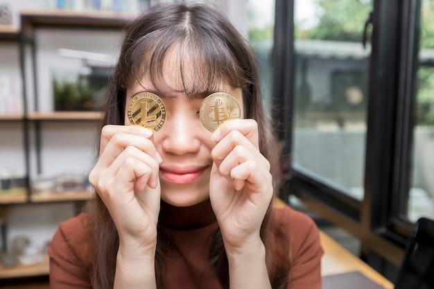 Femme d'affaires drôle tenant un bitcoin d'or et litecoin fermé son oeil