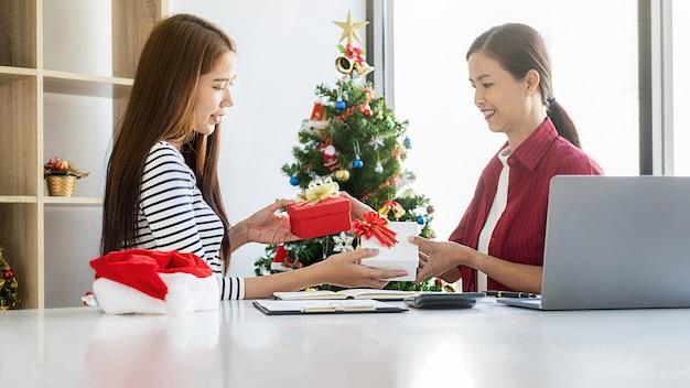 Femme d'affaires échangeant un cadeau au bureau le dernier jour ouvrable. les jeunes créatifs célèbrent les vacances dans un bureau moderne. joyeux noel et bonne année.