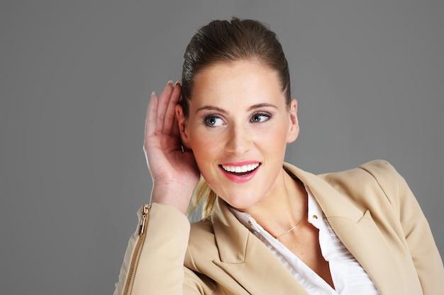 Une femme d'affaires écoutant sur fond gris