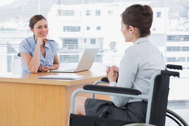 Femme d'affaires à l'écoute d'un candidat à un emploi handicapé