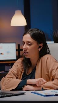 Femme d'affaires avec des écouteurs discutant des statistiques de marketing