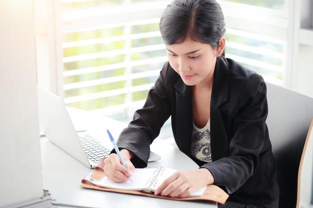 Femme d'affaires écrit sur un cahier avec un ordinateur portable