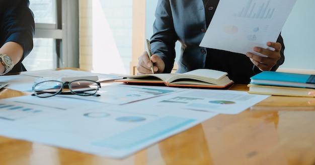 Femme d'affaires écrit à la main sur un bloc-notes avec un stylo dans la salle de réunion