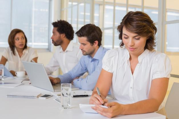 Femme d'affaires écrit des notes avec des collègues en réunion au bureau