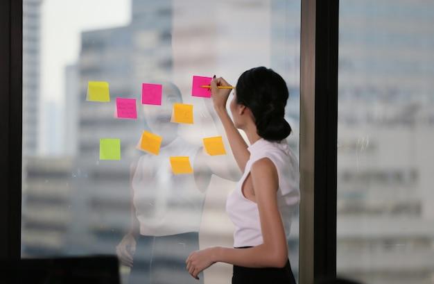 Femme d'affaires écrit des notes sur le papier attaché à la vitre