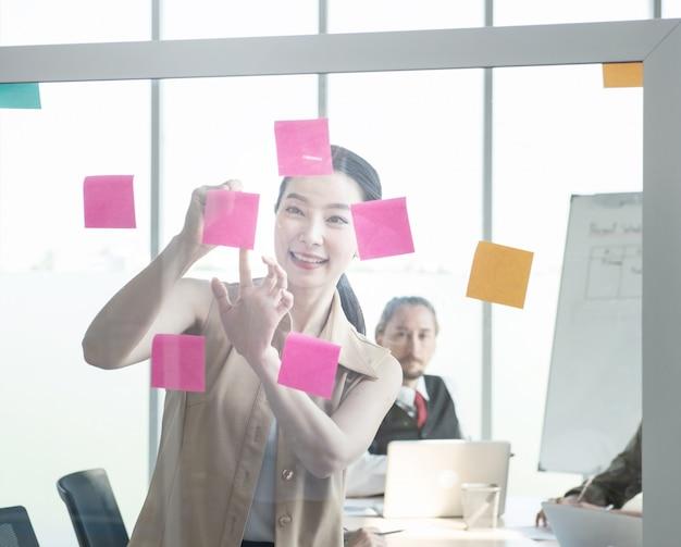 Femme d'affaires écrit des notes sur un papier collant