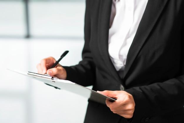 Une femme d'affaires écrit sur le presse-papiers avec un stylo noir