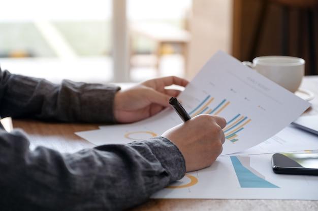 Une femme d'affaires écrit et travaille sur des données commerciales et des documents sur la table au bureau