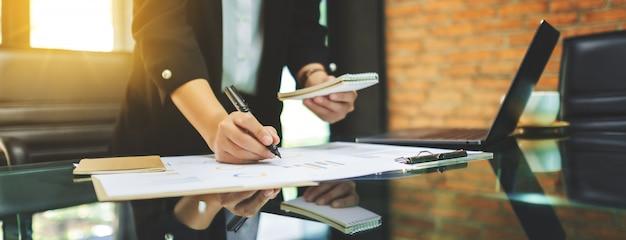 Une femme d'affaires écrit et travaille sur les données financières des entreprises et un ordinateur portable sur la table au bureau