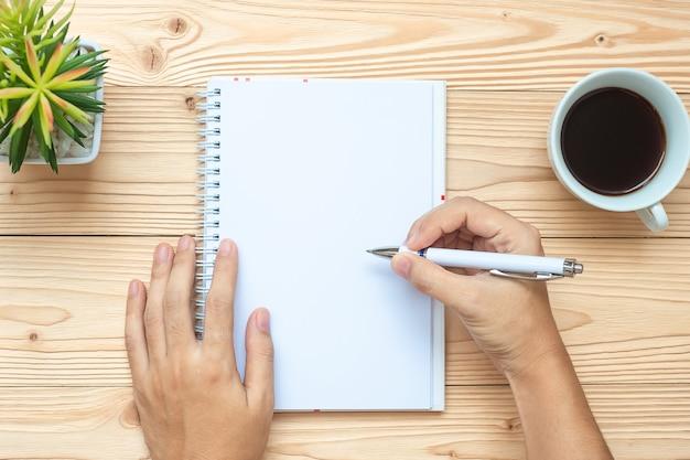 Femme affaires, écriture, à, cahier, tasse café noir