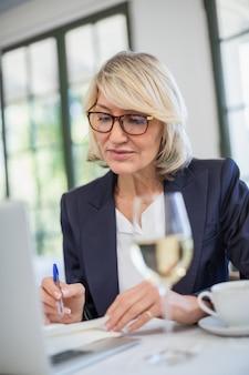 Femme affaires, écriture, journal, restaurant