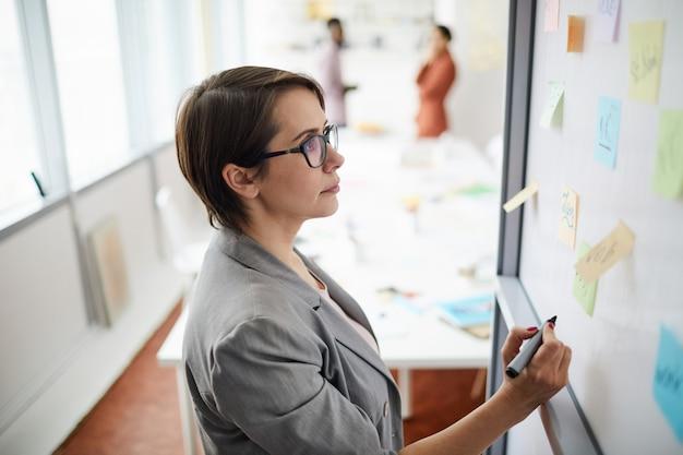 Femme affaires, écriture, tableau blanc