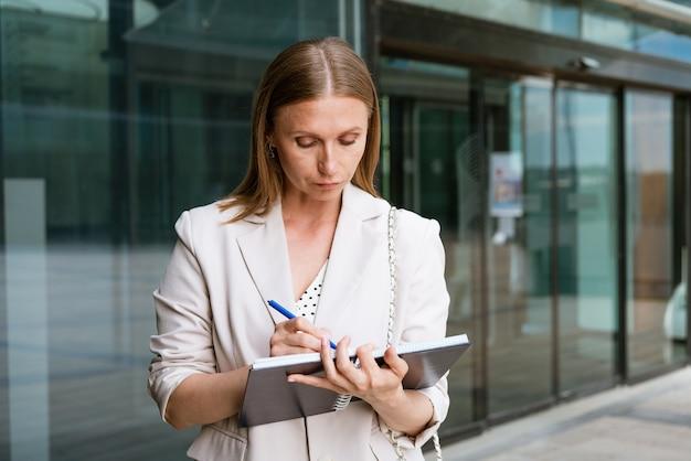 Femme d'affaires écrivant avec un stylo dans un cahier, une fille caucasienne réussie en veste légère se tient près d'un...