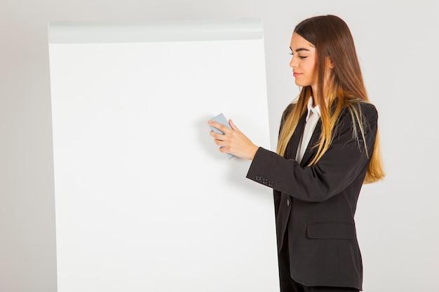 Femme d'affaires efface le tableau blanc