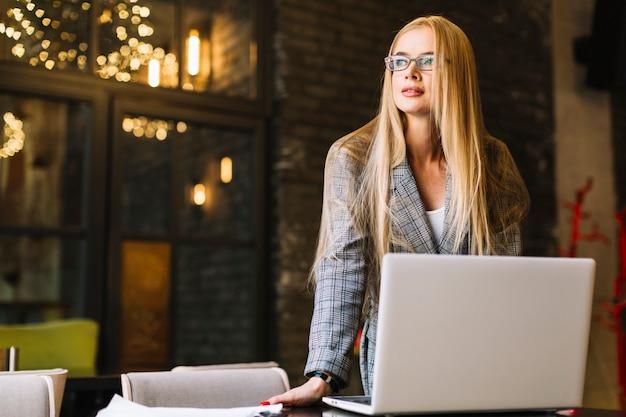 Femme d'affaires élégant avec un ordinateur portable dans un café confortable