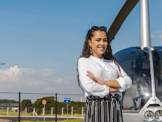 Femme d'affaires élégant près de l'hélicoptère. concept d'affaires, de succès et de luxe.