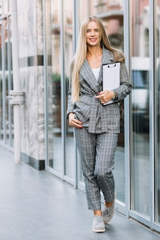 Femme d'affaires élégant avec le presse-papier en ville