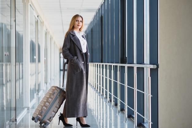 Femme d'affaires élégante avec des bagages à l'aéroport