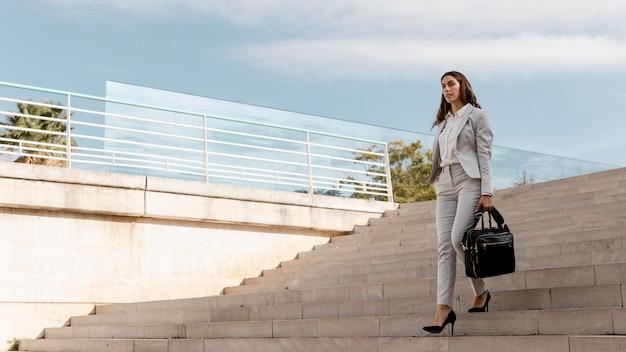 Femme d'affaires élégante dans les escaliers à l'extérieur avec sac et espace de copie