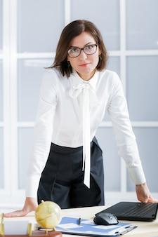 Femme d'affaires élégante dans des verres au bureau.