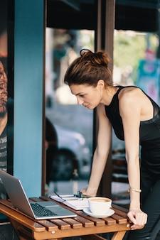 Femme d'affaires élégante debout près d'une table dans un café tout en regardant l'ordinateur portable