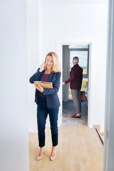 Femme d'affaires élégante. femme d'affaires élégante aux cheveux blonds parlant par téléphone sur son chemin pour travailler avec son charmant mari