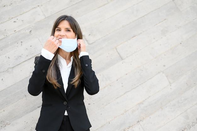 Femme d'affaires élégante mise sur un masque protecteur à l'extérieur