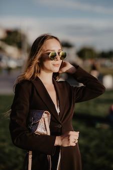 Femme d'affaires élégante portant des lunettes de soleil à la chaude journée d'été dans la ville